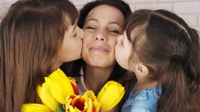 Mothers Day. Daughters Kiss Mother