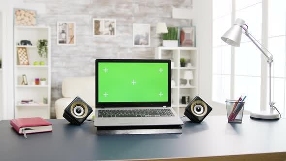 Thumbnail for Moderner Laptop mit grünem Bildschirm auf dem Tisch liegend