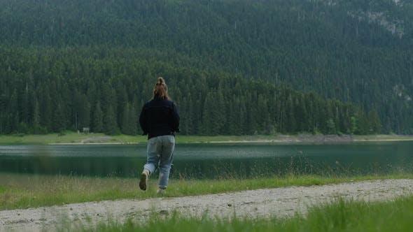 Back view of travel woman walking against Black Lake in Montenegro.