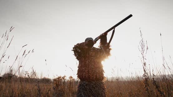 Thumbnail for Hunter Aims the Target With Rifle in the Field at Foggy Morning or Sunny Autumn Evening