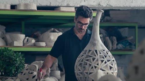 Male Ceramist Creating Clay Vessel in Studio