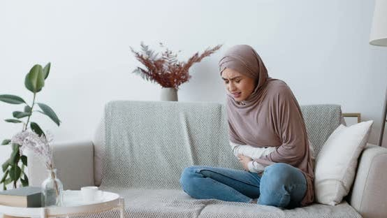 Muslim Woman Suffering From Abdominal Pain, Period Cramp, Sitting Alone on Couch at Home