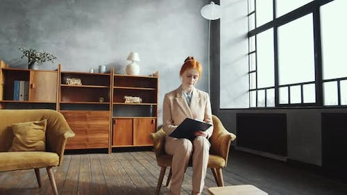 Female Psychologist Taking Notes and Planning Her Workday in Office