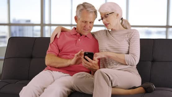 Thumbnail for Elderly couple sitting on couch using smartphone