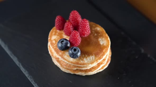 Timelapse of Fruit and Syrup Over Pancakes
