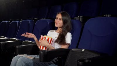 Attractive Young Woman Enjoying Movies at the Cinema