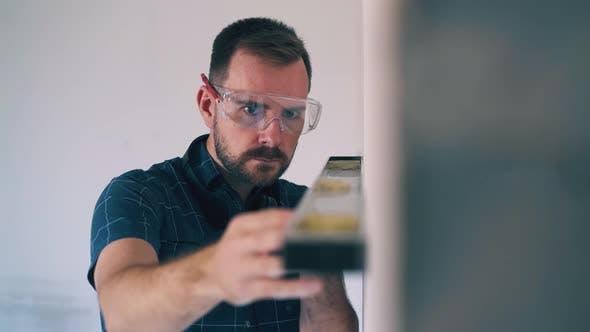 Thumbnail for Handyman in Goggle Checks Wall Level at Room Renewal