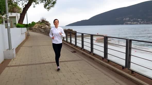 Thumbnail for Skinny Woman in Sportswear Running Along River Bank