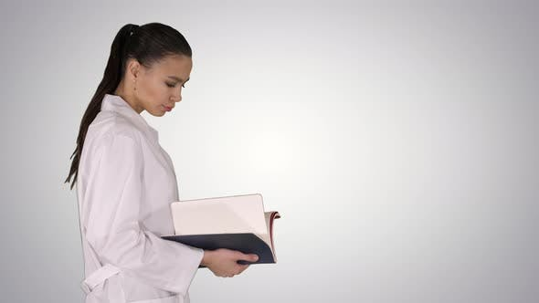 Thumbnail for Attractive Medicine Student or Doctor with Notebook Walking and Reading on Gradient Background.