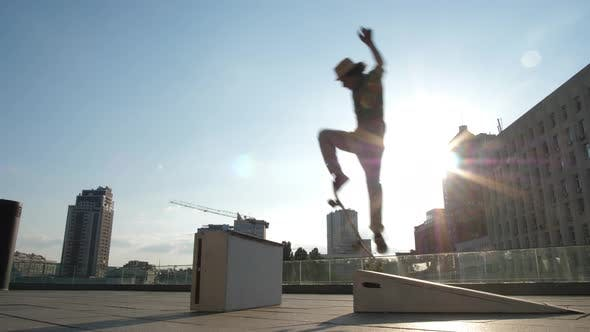 Cover Image for Active Skater Doing Ollie Trick Jumping Over Curb