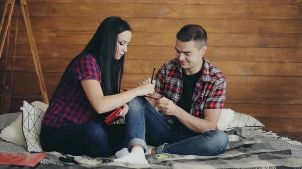 Thumbnail for Loving Couple are Sitting on a Bed and Carving Hearts with Scissors to Valentine's Day