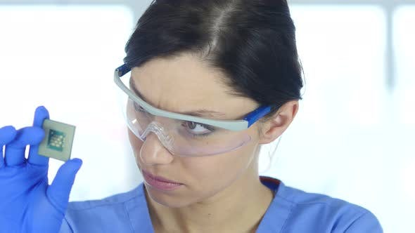 Thumbnail for Scientist in Protective Glasses Looking at Computer Chip