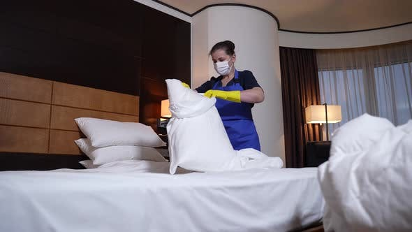 Hotel Maid in Mask and Gloves Changing Bed Linen