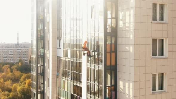Laborer in Orange Suit Washes Windows of Apartment Building