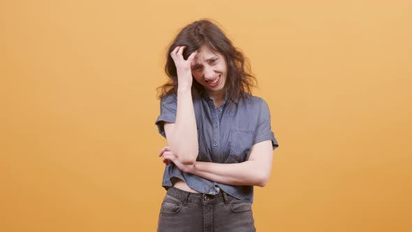 Thumbnail for Young Women Looking Worried or Upset Over a Yellow Background