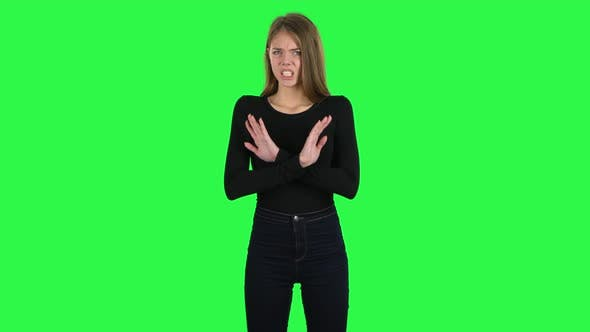 Cover Image for Young Woman Strictly Gesturing with Hands Crossed Making X Shape Meaning Denial Saying NO. Green