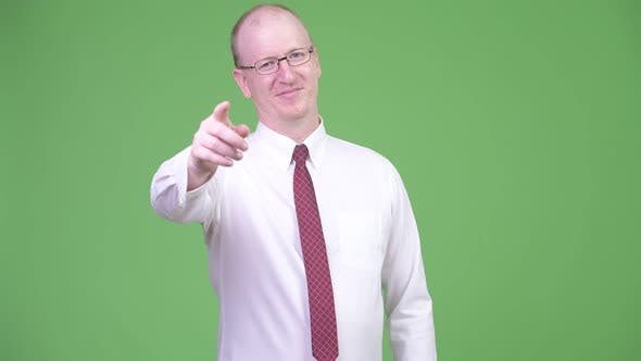 Thumbnail for Happy Mature Bald Businessman Pointing To Camera
