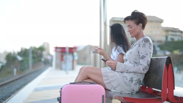 Thumbnail for Two Multi-ethnic Tourist Women Using Phone While Waiting At The Train Station
