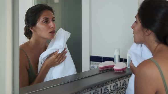 Woman Looking in Mirror and Wiping Face After Washing in the Morning