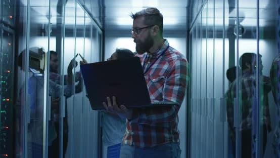 Thumbnail for Bearded IT Engineer Using Laptop in Server Room