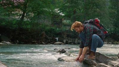 Man Sitting on Rock at River