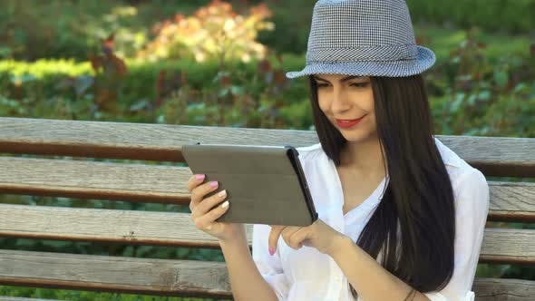 Thumbnail for Girl Uses Tablet on the Bench