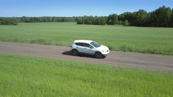 Thumbnail for Fast Car Speeds Along Path Between Boundless Green Fields