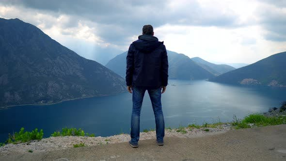 Cover Image for Man Standing on Mountain Peak Enjoys Mindblowing Landscape