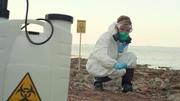 Female Scientist Examining Polluted Seashore
