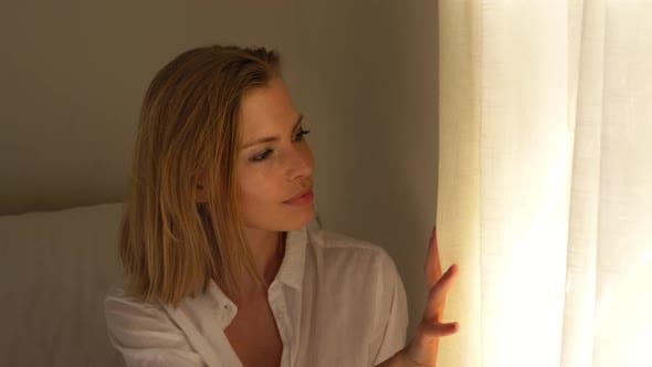 Magnifique modèle regardant à l'extérieur de la fenêtre de la chambre