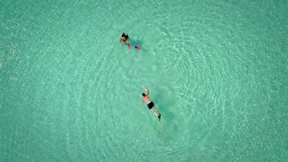 Thumbnail for Aerial view of man and woman swimming with masks and flippers in clear sea.