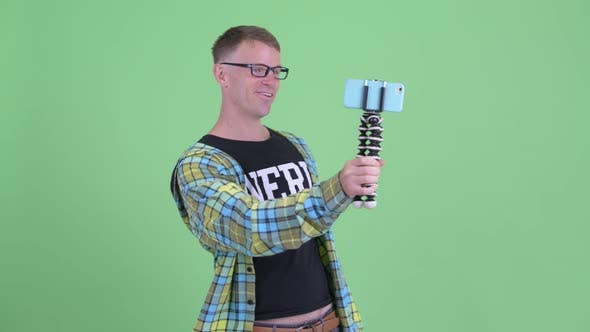 Thumbnail for Portrait of Happy Nerd Man Vlogging and Showing Phone