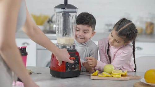 Unrecognizable Mother Turning on Blender As Son and Daughter Waiting for Healthful Vitamin Fruit