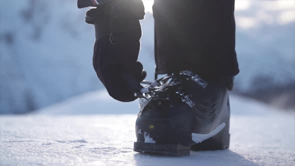 Thumbnail for A woman with ski boots preparing to go skiing in the snow at a ski resort.