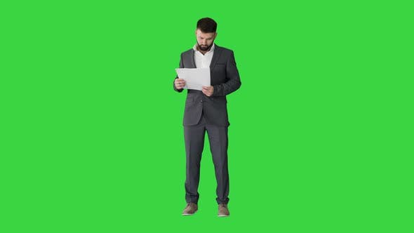 Thumbnail for Businessman Standing and Reading Papers Seriously on a Green Screen, Chroma Key.