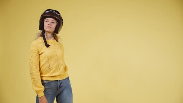 Thumbnail for Model in Yellow Top Posing with Hands on Hips Before Stylishly Removing Helmet