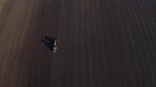 Cover Image for Aerial View Of Harvest Fields. Tractor Driving Across The Field.