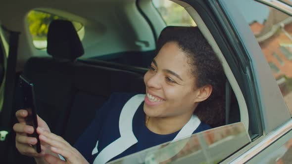 Thumbnail for Lovely Woman Networking on Phone in Car Backseat
