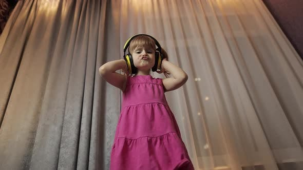 Thumbnail for Little Child Girl in Wireless Headphones Enjoying Listen Music. Dancing at Home