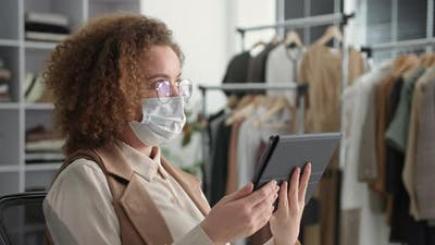 Portrait of a Young Woman in a Medical Mask and Glasses Uses a Tablet for Online Sales in an