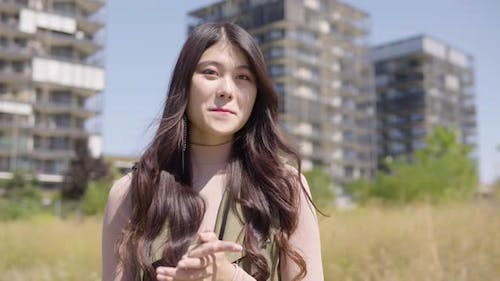 Young Asian Woman Applauds To Camera Smile  Apartment Building Complex