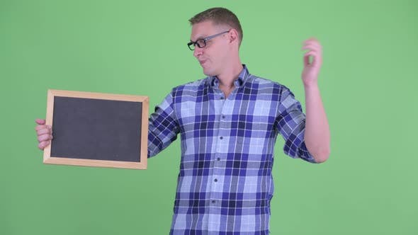 Thumbnail for Stressed Young Hipster Man Holding Blackboard and Giving Thumbs Down
