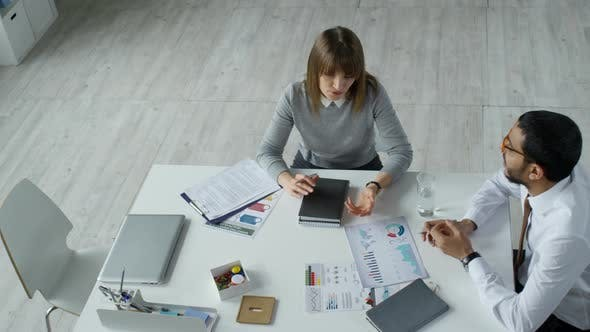 Thumbnail for High Angle of Businesswoman and Businessman Talking at Office Table