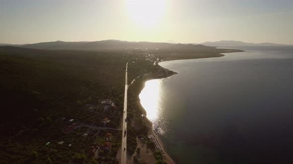 Thumbnail for Flying Over Sea and Coast with Road Along Waterfront. Trikorfo Beach, Greece