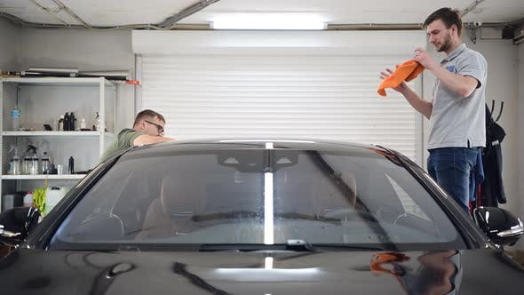 Two Specialist Dries the Car From Moisture Car Washing at Detailing Service