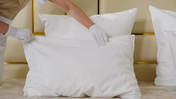 Hotel Cleaning Concept. Close-up View of Young Pretty Maid in Uniform Making Bed in Room Touching