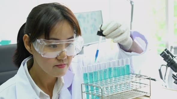 Asian scientist experimenting chemicals in science laboratory