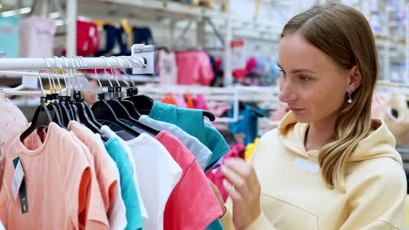 Thumbnail for Young Happy Woman Found Suitable Outfit for Your Child in a Children's Clothing Store