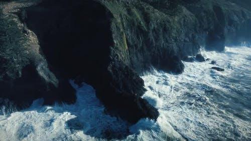 Drone Floating Over Coastline Rocks With Sea Waves Splashing Slow Motion