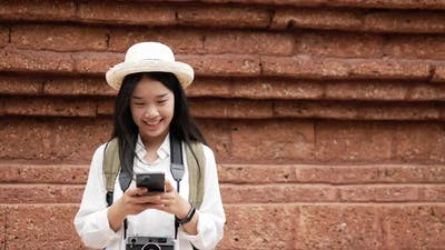 Woman standing and chatting on smartphone